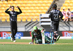 Pakistan's Sarfraz Ahmed, centre, is stumped by New Zealand's Glenn Phillips off the bowling of Mitchell Santner for 9 in the first T20 International Cricket match, Westpac Stadium, Wellington, New Zealand, Monday, January 22, 2018