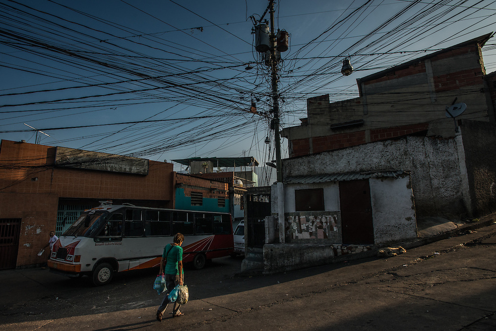 """CARACAS, VENEZUELA -MARCH 22, 2016: Residents of  Catia, a slum in Caracas that is regularly subject to state-mandated electricity rationing, walk past improvised electrical wiring. Venezuela is shutting down this week, as the government struggles with a deepening electricity crisis.  President Nicolas Maduro gave everyone an extra three days off work, extending the two-day Easter holiday, according to a statement in the Official Gazette published late last Tuesday.  The government has rationed electricity and water supplies across the country for months and urged citizens to avoid waste as Venezuela endures a prolonged drought that has slashed output at hydroelectric dams. The ruling socialists have blamed the shortage on the El Nino weather phenomena and """"sabotage"""" by their political foes, while critics cite a lack of maintenance and poor planning.  PHOTO: Meridith Kohut"""