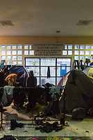 Migrants from various countries, including Syria and Iraq, camp out under an awning at the port in Mytilene, on the Greek island of Lesbos. They had arrived on Lesbos from Turkey, having paid smugglers a large amount of money to help them do the short but dangerous journey across the Aegean Sea. Here they wait to take a ferry to the Greek mainland to continue on to Germany and elsewhere.