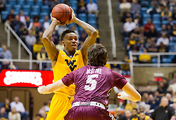 Dec 21, 2015; Morgantown, WV, USA; West Virginia Mountaineers guard Daxter Miles Jr. (4) passes over Eastern Kentucky Colonels guard Isaac McGlone (5) during the first half at the WVU Coliseum. Mandatory Credit: Ben Queen-USA TODAY Sports