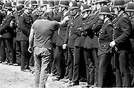 A striking miner points at a policeman at Orgreave. 4 June 1984