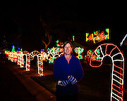Photographed as we enjoyed the holiday displays in the Winterhaven neighborhood.  I asked Robin to pose in front of the candy cane lights.  This is the only image made with a hand held camera this week.  I needed to increase the ISO setting to ISO 2000 and opened my aperture to f/3.2.  This allowed me to have a 1/60 sec exposure which was fast enough to ensure a sharp exposure.  I also used a small LED light panel to illuminate Robin otherwise she would have been too dark in the frame.<br />