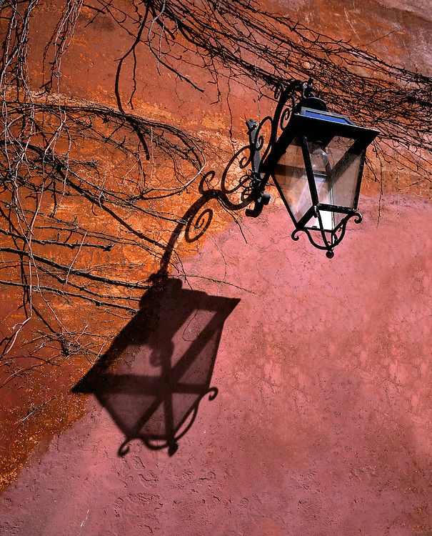Afternoon light casts an intricate shadow from a wrought-iron street lantern onto a stucco wall in Rome, Italy.