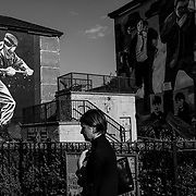 "A woman walks past murals depicting scenes from the Troubles found in the Bogside, a Catholic enclave of Londonderry, Northern Ireland. This city is considered a ""front-line"" of Britain's push to leave the E.U. Northern Ireland, September 2019"