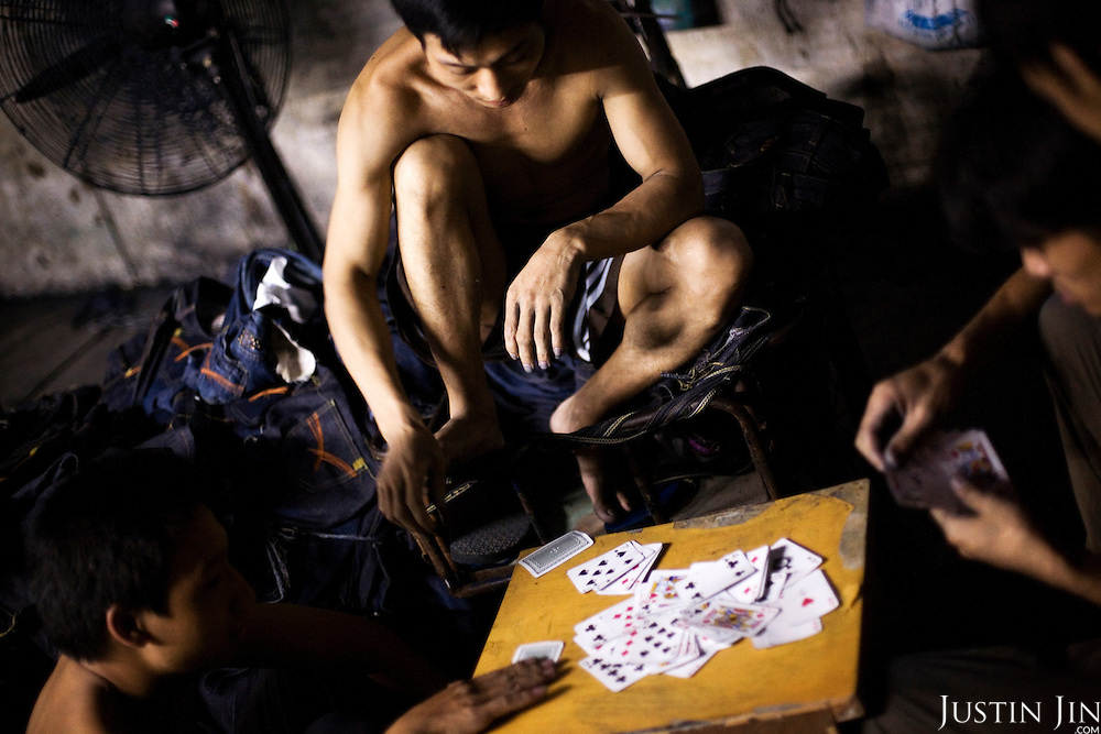 """Workers play cards in Mr Huang's factory in Zhongshan city, China..This picture is part of a photo and text story on blue jeans production in China by Justin Jin. .China, the """"factory of the world"""", is now also the major producer for blue jeans. To meet production demand, thousands of workers sweat through the night scrubbing, spraying and tearing trousers to create their rugged look. .At dawn, workers bundle the garment off to another factory for packaging and shipping around the world..The workers are among the 200 million migrant labourers criss-crossing China.looking for a better life, at the same time building their country into a.mighty industrial power."""