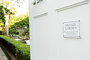 A private garden and sign on Meeting Street in Charleston, SC.