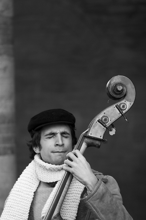 Black and white photography. A street musician in Bologna.