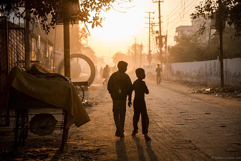 Kids walking at sunrise in a dirt road. Varanasi, India