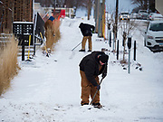 11 JANUARY 2020 - DES MOINES, IOWA:  Workers shovel snow off the sidewalks of the East Village in Des Moines Saturday. The first significant snow in two months blanketed Des Moines Friday evening into Saturday morning. Meteorologists predicted up to six inches of snow overnight but by Saturday morning only about 3 inches had fallen in central Des Moines.     PHOTO BY JACK KURTZ