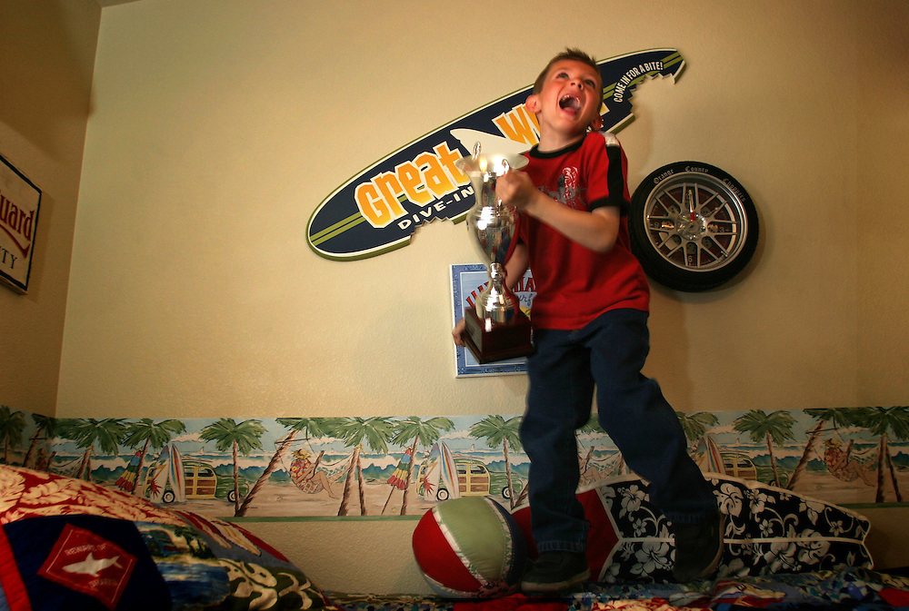Cruz Fiore, 7 years-old, jumps on his bed while holding one of his racing trophies in his family's home in Henderson, NV on Monday, March 5, 2007. Cruz is a professional go kart driver. He has won competitions in Nevada and California. His kart is painted with zebra stripes.