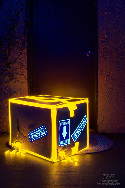 "A cardboard box bound with glowing tape and marked ""Fragile"" leaks glowing packing peanuts at the foot of a door. Blacklifght photography."