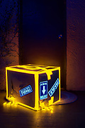 """A cardboard box bound with glowing tape and marked """"Fragile"""" leaks glowing packing peanuts at the foot of a door. Blacklifght photography."""