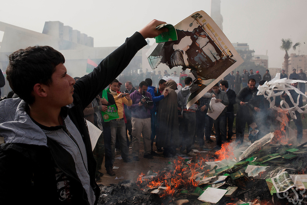 A Libyan opposition protester burns an image of Muammar el-Qaddafi  in front of a burning pile of books and posters during a protest in the eastern city of Benghazi, Libya March 02, 2011. March 02 is traditionally a celebration of the People's Authority Day in Libya, and protesters marked the occasion by burning Qaddafi books, speeches and images. .Slug: Libya.Credit: Scott Nelson for the New York Times