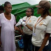 Jina Guillet, 27, a nurse with CARE works with the health team to distribute delivery kits to pregnant women like Sophia Robert in Delmas 31 camp. The delivery kits include plastic sheeting, gloves, razor, and gauze, to help women deliver more safely in emergency situations. Sophia is 21 and pregnant with her first child. She lost her home in the earthquake and doesn't have a tent of her own. She is living in a friend's tent with her mother. Her baby is due in the beginning of february.