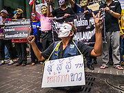 """02 JUNE 2013 - BANGKOK, THAILAND: A legless man clenches his fists while he leads a protest march through the Bangkok skywalk system. About 300 people wearing the Guy Fawkes mask popularized by the movie """"V for Vendetta"""" and Anonymous, the hackers' group, marched through central Bangkok Sunday demanding the resignation of Prime Minister Yingluck Shinawatra. They claim that Yingluck is acting as a puppet for her brother, former Prime Minister Thaksin Shinawatra, who was deposed by a military coup in 2006 and now lives in exile in Dubai.      PHOTO BY JACK KURTZ"""