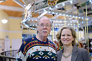 "Garden City, New York, USA. March 9, 2019. R-L, Nassau County Executive LAURA CURRAN and BOB STUHMER pose in front of Nunley's Carousel during Unveiling Ceremony of mural by painter Michael White. Stuhmer arranged all the organ music for the carousel, including the instrumental piece Billy Joel wrote ""Waltz #1 (Nunley's Carousel)"" in 2001.  Event was held at historic Nunley's Carousel in its Pavilion on Museum Row on Long Island."