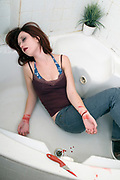 Mock-up of a Young woman in her 20s in a household bathtub in an attempt to commit suicide