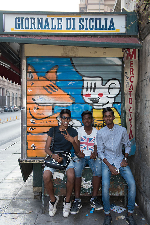 Like all the boys of thiergeneration, these three Bengali guys love to be photographed, even without asking a contact for to have the pic. , these three Bengali in central Palermo waiting for the bus leaning on a closed newsstand, talking to each other in Sicilian
