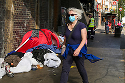 © Licensed to London News Pictures. 18/09/2020. London, UK. A woman wearing a face covering walks past a homeless person sleeping in a tent under a bridge in London. The government figures reveal that coronavirus cases, hospital admissions and deaths are on the rise and Prime Minister, BORIS JOHNSON refused to rule out a second national lockdown. It has been reported that rates of COVID19 infection is more likely to increase in over 50 year olds. Photo credit: Dinendra Haria/LNP