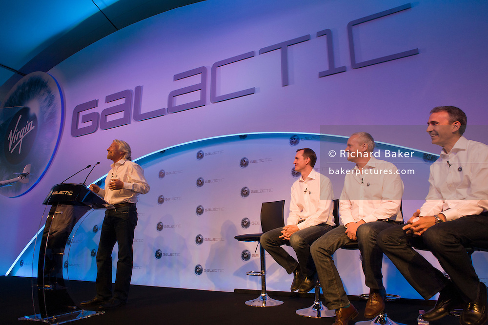 Virgin Galactic's Richard Branson speaks to audience alongside other executives during announcement presentation.