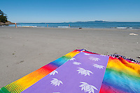 A colorful mexican blanket is set on a sandy low-tide beach at Arbutus Cove, near Victoria, BC, Canada.
