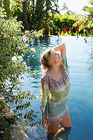 Young woman with hand on head standing in natural swimming pool portrait