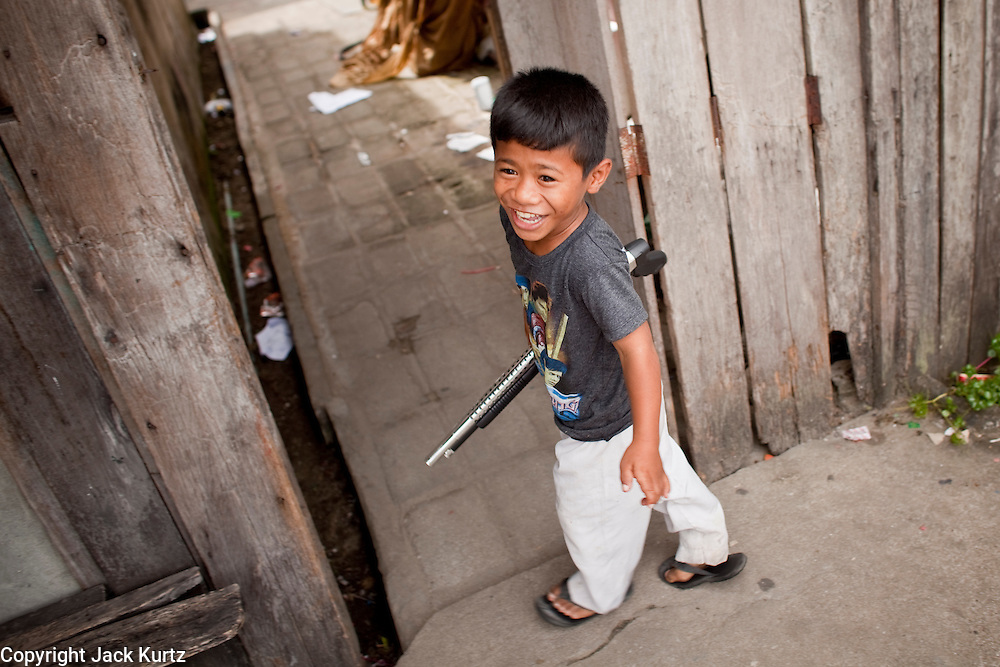 "Sept. 27, 2009 -- TAK BAI, THAILAND: Thai Muslim boys play with toy shotguns in front of their home in Tak Bai, Narathiwat, Thailand. Thailand's three southern most provinces; Yala, Pattani and Narathiwat are often called ""restive"" and a decades long Muslim insurgency has gained traction recently. Nearly 4,000 people have been killed since 2004. The three southern provinces are under emergency control and there are more than 60,000 Thai military, police and paramilitary militia forces trying to keep the peace battling insurgents who favor car bombs and assassination.   Photo by Jack Kurtz / ZUMA Press"