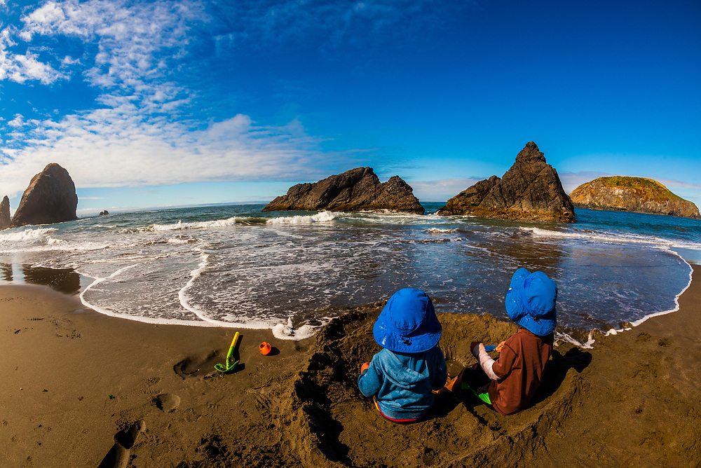 4 and 6 year old brothers playing on the beach at Harris Beach State Park, Brookings, Oregon USA.