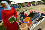 Women selling food from the back of a motorbike inside the Long Barracks -housing the survivors of Tsunami in Banda Aceh. Martine Perret