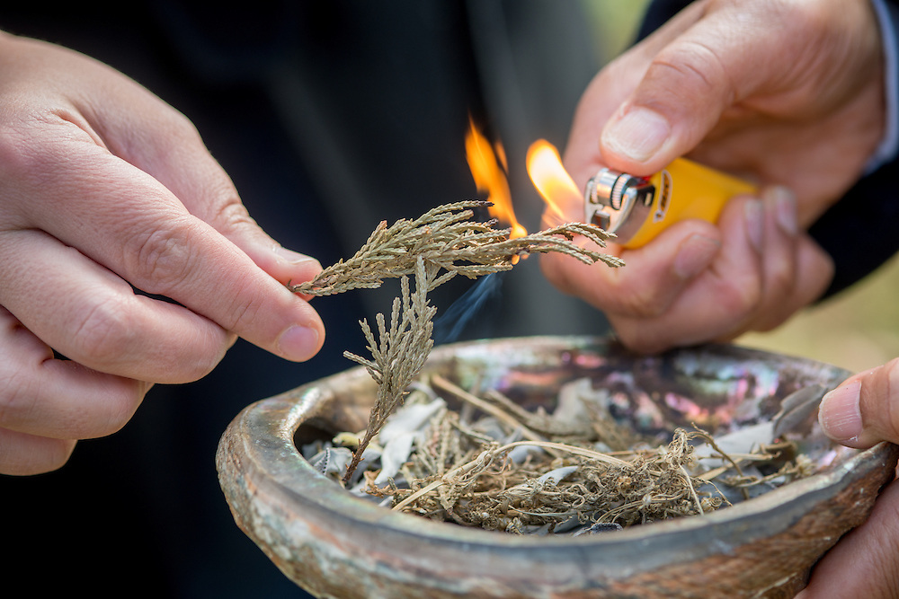 Hands using a lighter to burn ceremonial herbs and leaves at the Piscataway Indian Nation burial grounds, Accokeek, Maryland