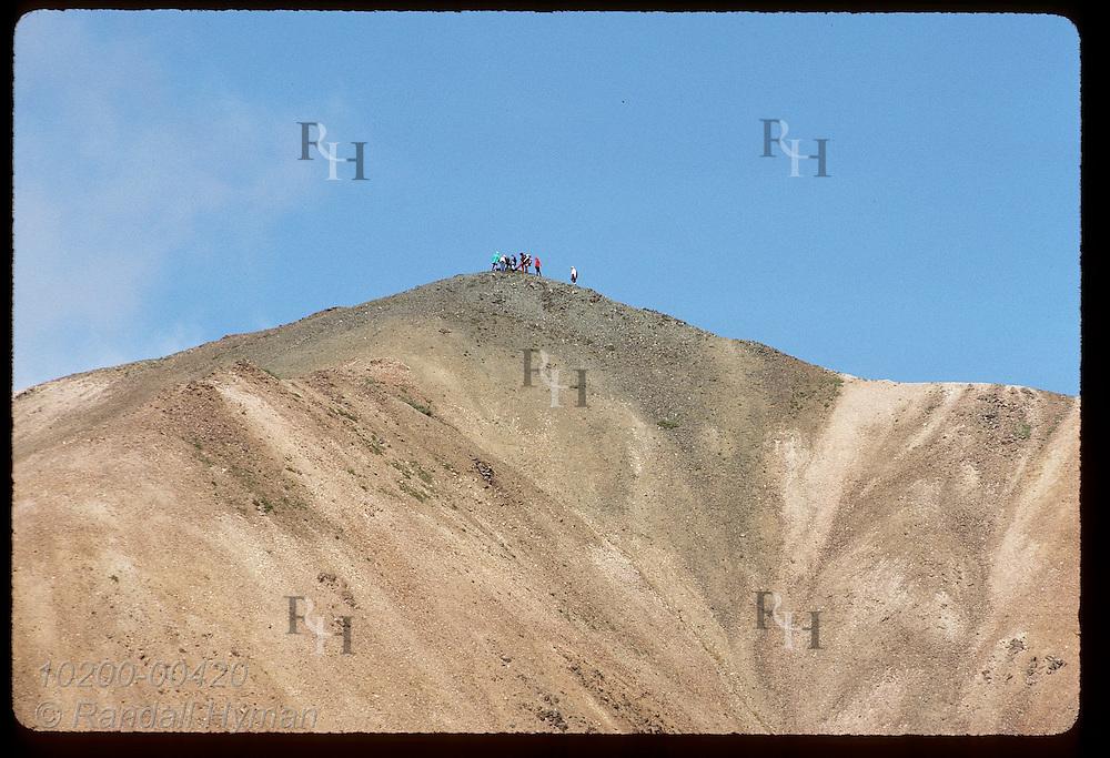 Hikers on Park Service nature walk stand atop red-gray ridge of volcanic soil; Denali National Park, Alaska