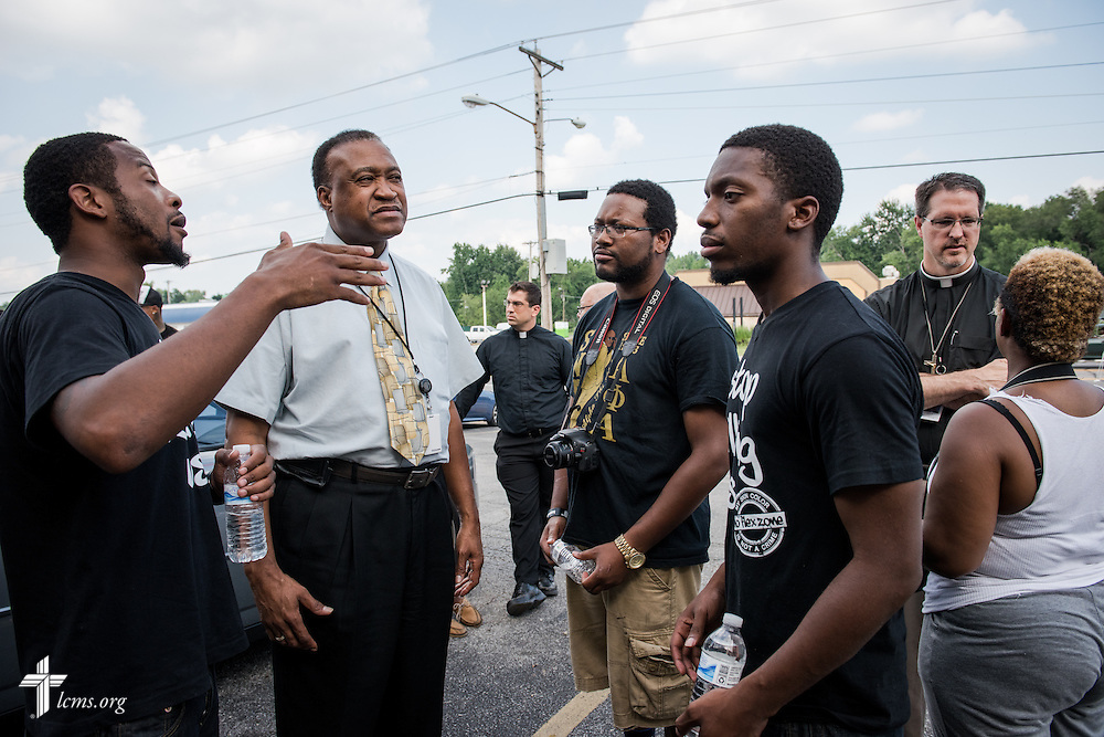 The Rev. Roosevelt Gray, director of LCMS Black Ministry (with tie), and the Rev. Steve Schave, director of LCMS Urban and Inner City Mission (far right) talk to members of the community along West Florissant Avenue on Monday, August 18, 2014, in Ferguson, Mo. LCMS Communications/Erik M. Lunsford
