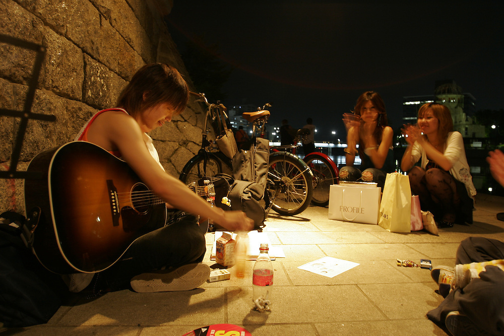 Hiroshima, Young people play music under the Motoyasu Bashi (bridge) on the Motoyasu-Gawa river in site of the a bomb dome at the Peace Memorial Park A nightlygathering spot for many young People.