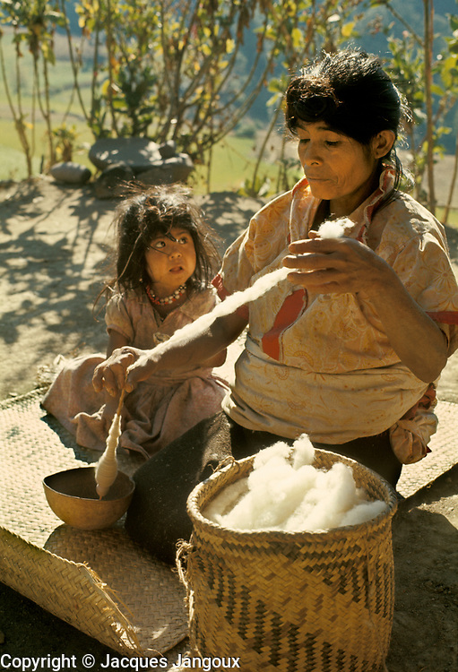 Latin America, Mexico, Oaxaca State, Mixtec Indian woman spinning cotton with daughter watching.