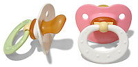 two gerber baby pacifiers pink and green and white
