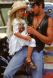 motorcycle rider holding a little girl in dressy clothes and a rose in hand