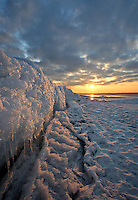 A beautiful and dramatic winter sunrise illuminates interesting patterns and textures of snow and ice with  warm and golden light. Taken on the frozen surface of Lake Ontario in Kingston, Ontario, Canada.