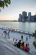 Brooklyn, NY - 9 September 2017. Spectators watch the last glow of sunset over the East River and the skyline of lower Manhattan from the Granite Overlook at Brooklyn Bridge Park.