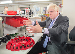 © Licensed to London News Pictures. 08/10/2014. Richmond, UK. Boris Johnson makes a wreath of poppies. The Mayor of London, Boris Johnson, and Zac Goldsmith MP tour 'The Poppy Factory' in Richmond, Surrey, today 9th October 2014.  Melanie Waters, the Chief Executive, briefed the Mayor and Zac Goldsmith on The Poppy Factory's 'Getting You Back to Work' initiative. To date, The Poppy Factory has supported nearly 500 wounded, injured or sick ex-service men and women back into the workplace through this new, nationwide initiative, through connections with commercial organisations like Transport for London. The goal is to help over 1,000 veterans by 2018. Employees at The Poppy Factory have made some 13 million poppies, 950,000 thousand remembrance crosses and 96,000 wreaths for The Royal British Legion Remembrance events in November. The Annual Field of Remembrance at Westminster Abbey is also planned and delivered by The Poppy Factory. Photo credit : Stephen Simpson/LNP