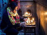 07 MARCH 2017 - KATHMANDU, NEPAL: A woman lights prayer candles at the Kamaladi Ganesh Temple, the most important Hindu temple dedicated to Ganesh, known as the overcomer of obstacles, in Kathmandu. In Hindu theology, Tuesdays are the best day to pray to Ganesh and the temple is very busy on Tuesdays. People frequently visit temples dedicated to Ganesh when they buy a new home or start a new job.     PHOTO BY JACK KURTZ