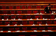 An usher clears tea cups from the stage where leaders sat, at the end of the  National People's Congress at the Great Hall of the People, after the annual session's final day in  Beijing, China, Friday, March 13, 2009.The Great Hall of the people's with it's impressive Stalinist building style and attention to protocol remains as one of the the country's last showcases  of old style communism on a grand scale.