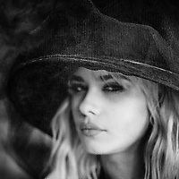 Vignetted shot of blonde female model wearing a hat shot through a veil eyes open
