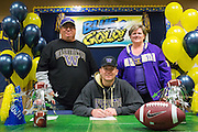 Jason Scempos and his parents pose with a duplicate National Letter of Intent to play football at the University of Washington during the NCAA National Signing Day event at Milpitas High School in Milpitas, California, on February 4, 2015. (Stan Olszewski/SOSKIphoto)