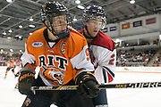 RIT Senior Captain Matt Garbowsky and Brock University's Anthony Geldart fight for a puck in the corner during a game at the Gene Polisseni Center on Saturday, October 4, 2014.