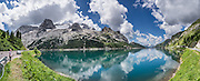 Marmolada reflects in Lago di Fedaia, a two-part reservoir just west of Passo di Fedaia (2057 meters or 6749 feet) along Strada Statale 641, at the head of Val di Fassa, in the Veneto region of Italy, Europe. Marmolada (Queen of the Dolomites) is capped by the biggest (and only skiable) glacier in the Dolomiti: Ghiacciaio della Marmolada. Known as Marmoleda in Ladin, the highest peak in the Dolomites rises to 3343 meters (10,968 feet) elevation at Punta Penia. The World War I museum at Serauta lift station describes the amazing City of Ice (Die Eisstadt or Citta di Ghiaccio, 1917), where Austrian soldiers inside the Marmolada Glacier built quarters in tunnels extending 12 kilometers with a vertical drop of over 1000 meters! Nine thousand Austrian and Italian soldiers died on the front line in a stalemate on and around Marmolada over 2 years. After Austria lost World War I, its South Tirol became Italy's Trentino-Alto Adige/Südtirol region (bordering the Veneto). The Dolomites are part of the Southern Limestone Alps, in Europe. UNESCO honored the Dolomites as a natural World Heritage Site in 2009. This panorama was stitched from 8 overlapping photos.