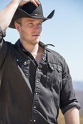 hot masculine cowboy with blue eyes and blond hair outdoors