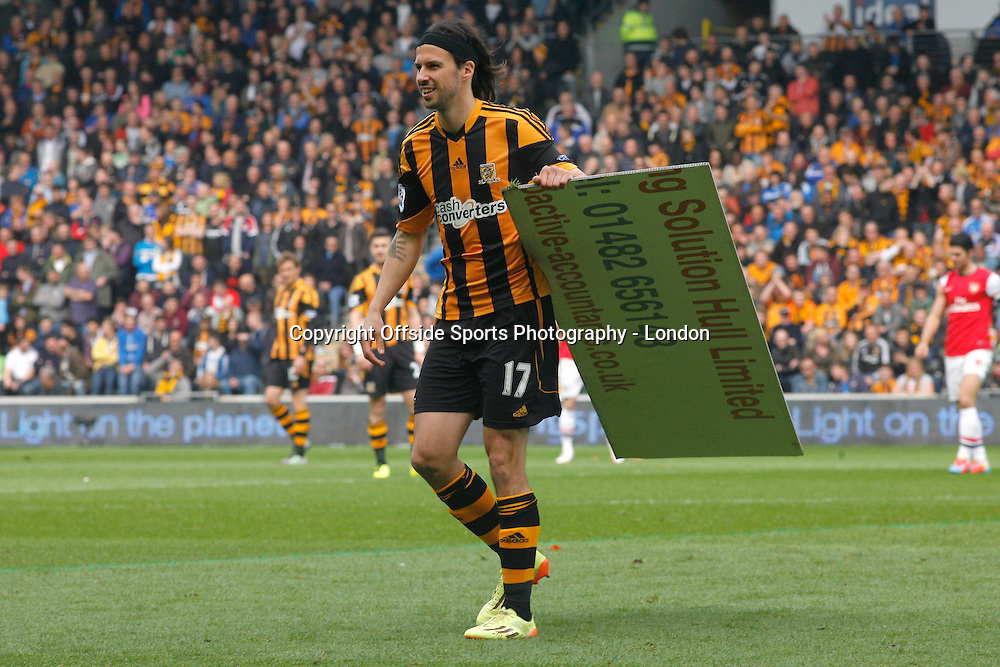 20 April 2014 Premier League Football Hull City v Arsenal -<br /> George Boyd of Hull carries off part of an advertising hoarding that blew onto the pitch.<br /> Photo: Mark Leech