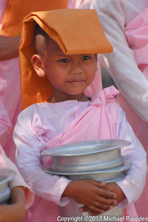 """A young Burmese nun collects alms with a group of other """"sisters"""". Collecting alms amonst Buddhists is not considered begging, as much as providing an opportunity for others to give. Many young Buddhist children from Burma (Myanmar) spend part some of their younger years as nuns (girls) and monks (boys)."""