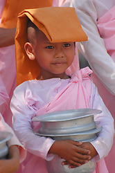 "A young Burmese nun collects alms with a group of other ""sisters"". Collecting alms amonst Buddhists is not considered begging, as much as providing an opportunity for others to give. Many young Buddhist children from Burma (Myanmar) spend part some of their younger years as nuns (girls) and monks (boys)."