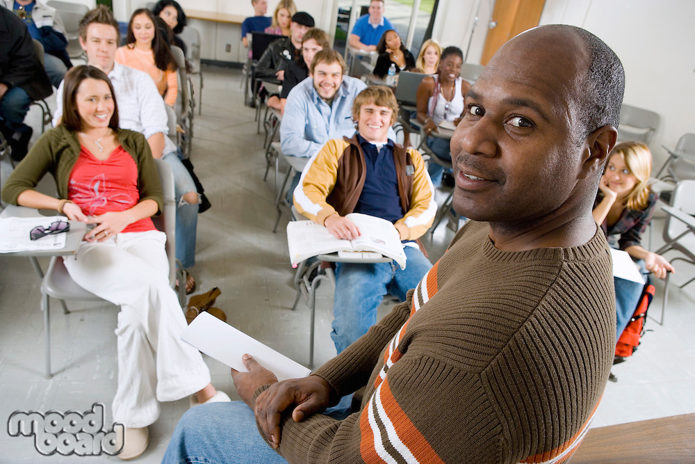 Teacher sitting in front of class (portrait)